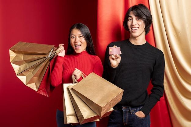 Couple souriant posant avec des sacs pour le nouvel an chinois Photo gratuit