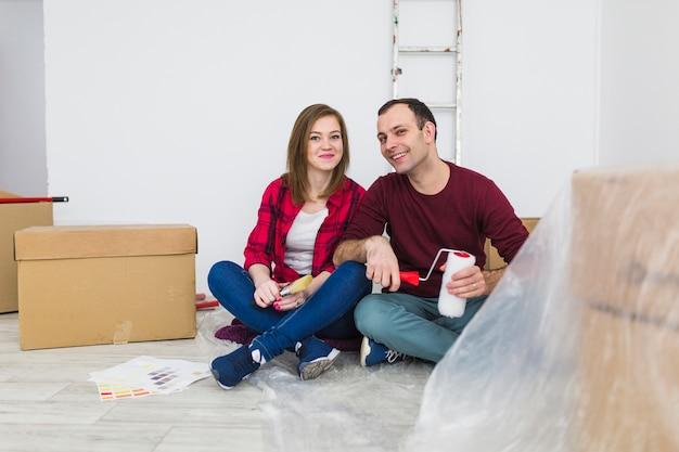 Couple souriant, reposant sur le sol pendant la rénovation Photo gratuit