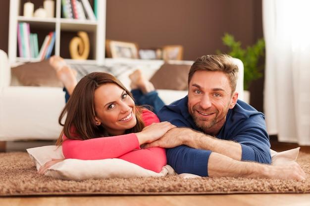 Couple Souriant Reposant Sur Un Tapis à La Maison Photo gratuit