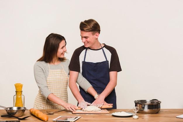 Couple souriant, rouler la pâte ensemble Photo gratuit