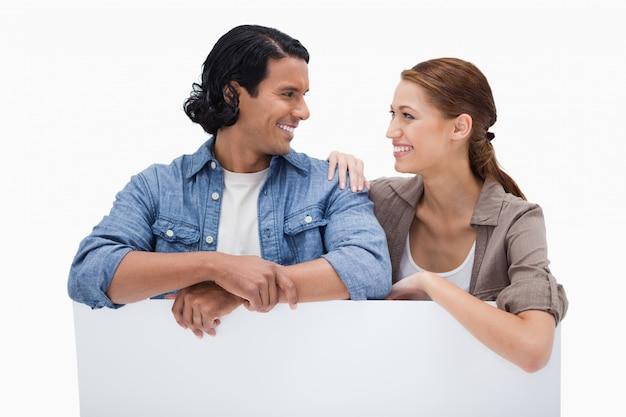 Couple souriant, s'appuyant sur un mur blanc Photo Premium
