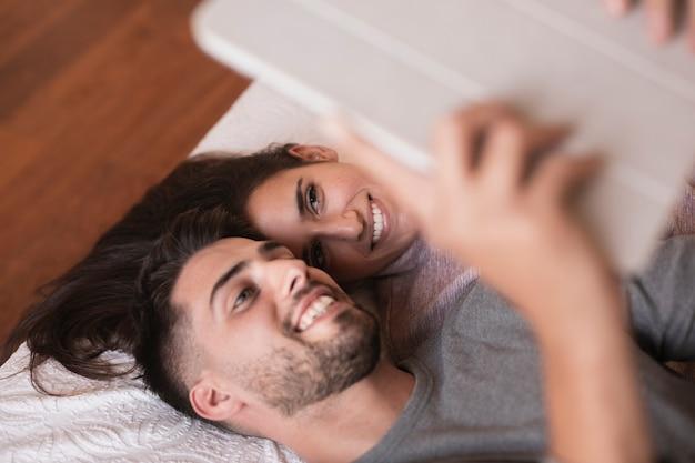 Couple souriant à la tablette Photo gratuit