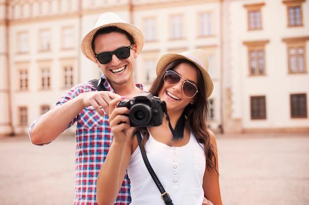 Couple Souriant, Visionnage De Photos Sur L'appareil Photo Photo gratuit