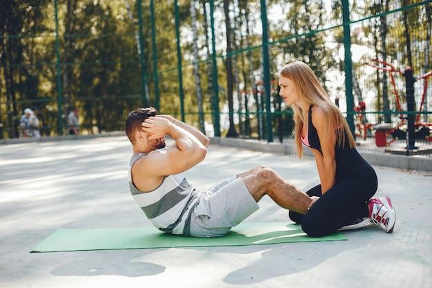 Couple sportif dans un parc d'été du matin Photo gratuit