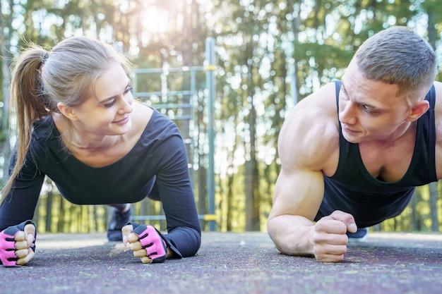 Couple sportif, faire de l'exercice de planche à l'extérieur Photo Premium