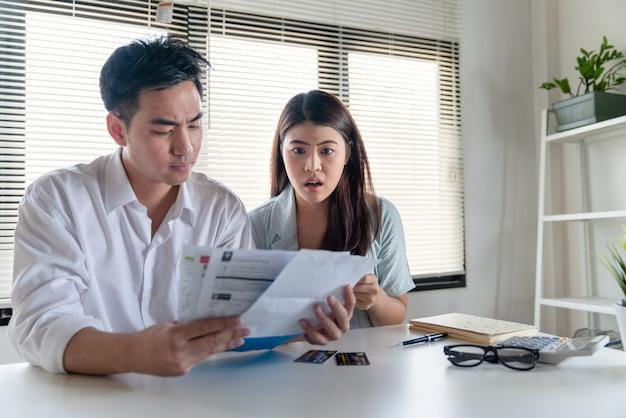 Couple de stress jeune mari et femme de famille à la recherche de nombreuses factures de dépenses telles que la facture d'électricité Photo Premium