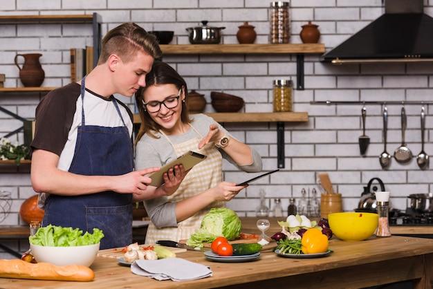Couple, tablette surf, et, cuisine, ensemble Photo gratuit