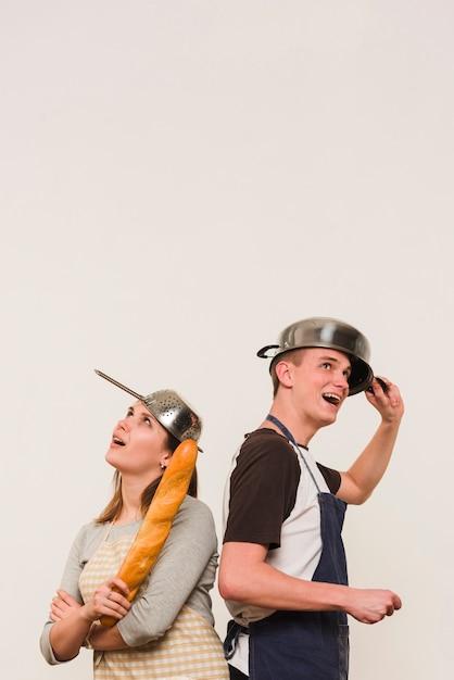 Couple en tablier debout avec batterie de cuisine sur la tête Photo gratuit