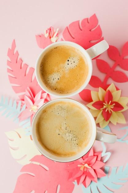 Couple de tasses blanches avec café sur fond pastel rose avec des fleurs d'artisanat en papier moderne origami Photo Premium