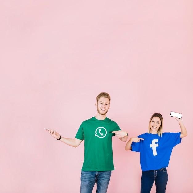 Couple avec téléphone portable pointant sur leur t-shirt avec facebook et icône whatsapp Photo gratuit