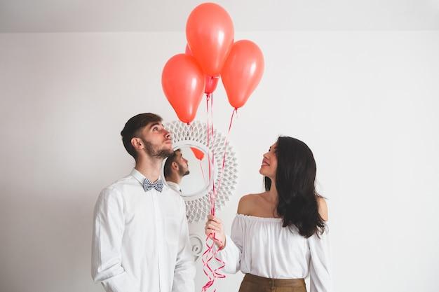 Couple Tenant Des Ballons Avec Forme De Coeur Photo gratuit