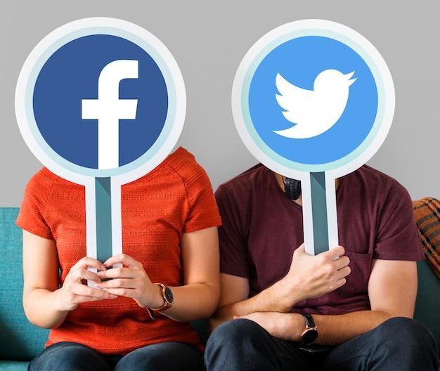 Couple tenant des icônes de médias sociaux Photo gratuit