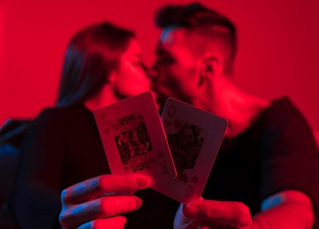 Couple, tenue, roi, reine, de, coeurs, jouer cartes, dans mains Photo gratuit