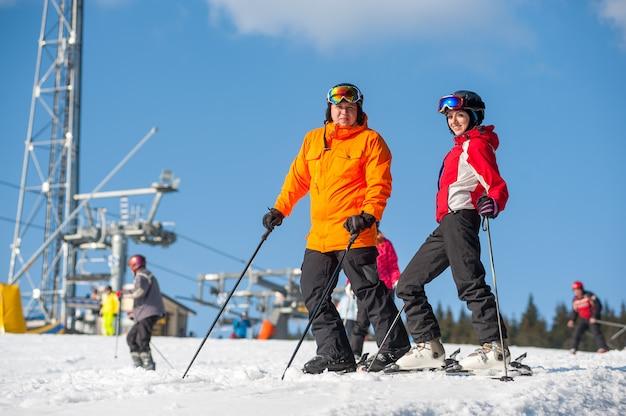 Couple, tenue, skis, debout, sommet, montagne, ensemble, hiver, station, remonte-pente, ciel bleu Photo Premium