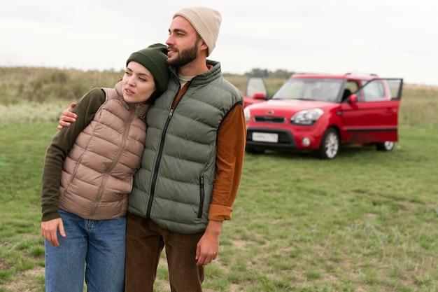 Couple De Tir Au Milieu Embrassant Devant La Voiture Photo Premium