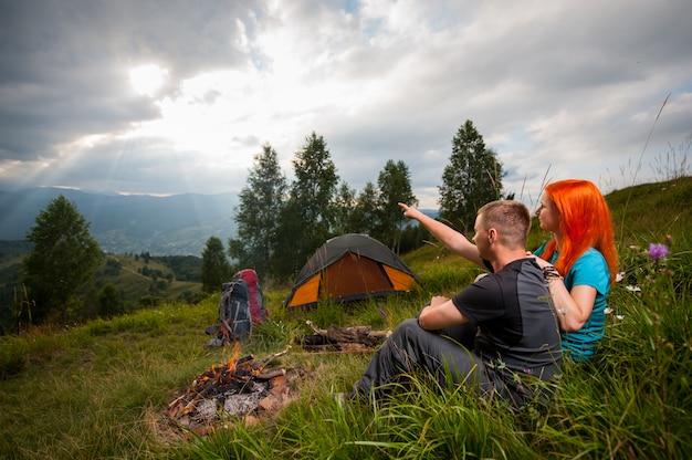 Couple de touristes assis sur l'herbe verte près du feu de camp Photo Premium