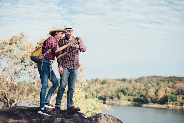 Couple de touristes avec des photographies sur la montagne Photo gratuit