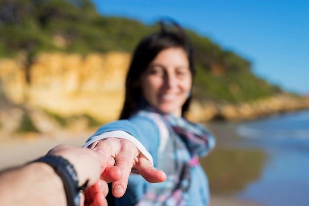 Couple De Touristes S'amusant Avec Une Femme Tenant L'homme Par La Main Et Tirant Vers La Mer Photo Premium