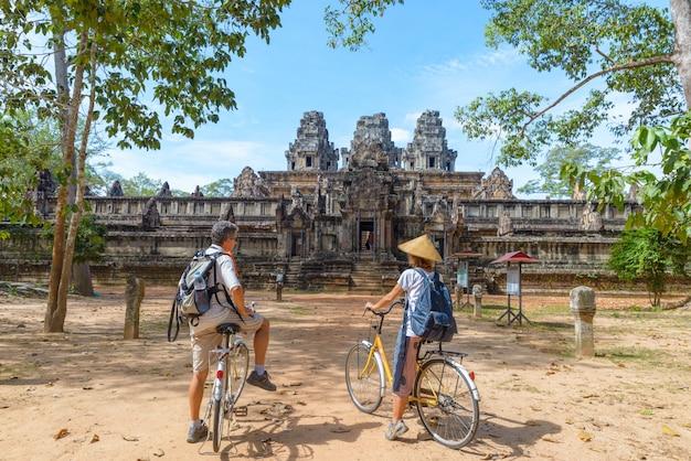 Couple de touristes à vélo autour du temple d'angkor, cambodge. ruines de ta keo Photo Premium