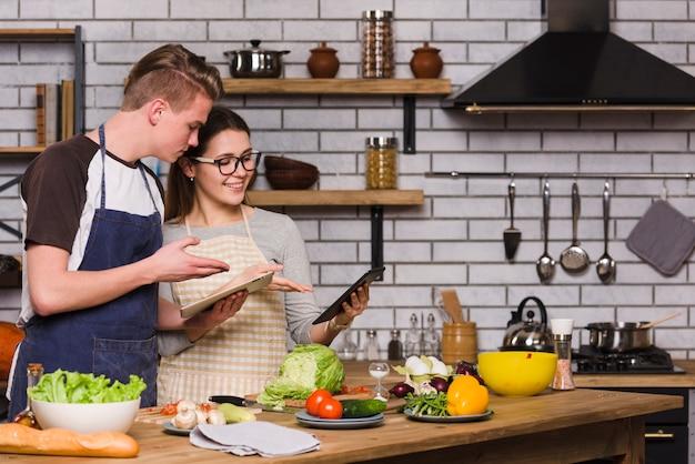 Couple utilisant des tablettes numériques tout en préparant des aliments Photo gratuit