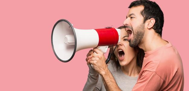 Couple, valentin, crier, par, porte-voix, fond rose, isolé Photo Premium