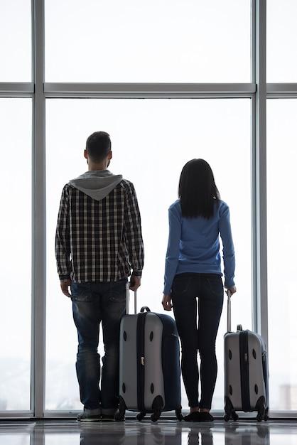 Couple Avec Valises Regarde Par La Fenêtre De L'aéroport. Photo Premium