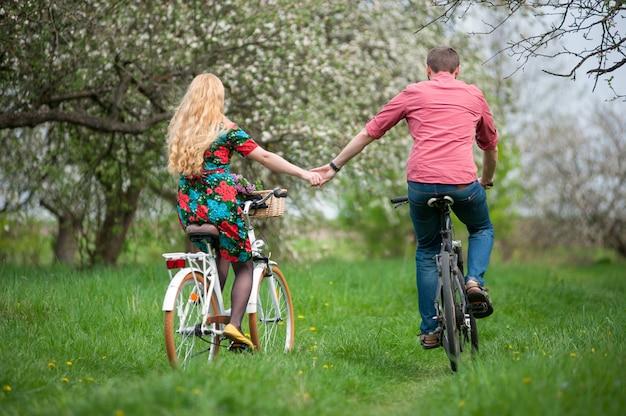 Couple à vélo dans le jardin de printemps Photo Premium
