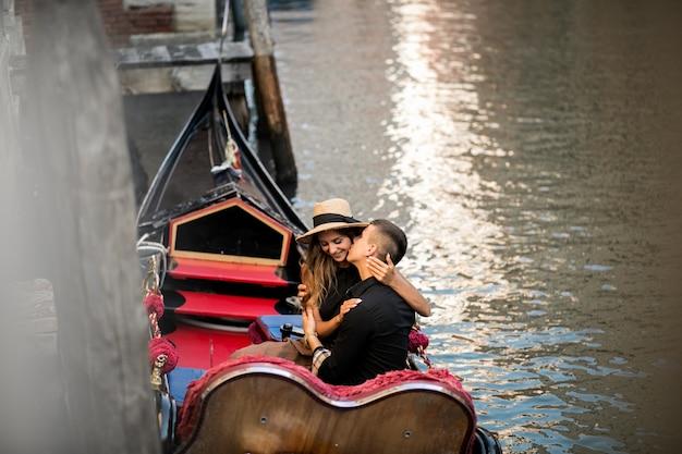 Couple à venise assis en gondole Photo gratuit