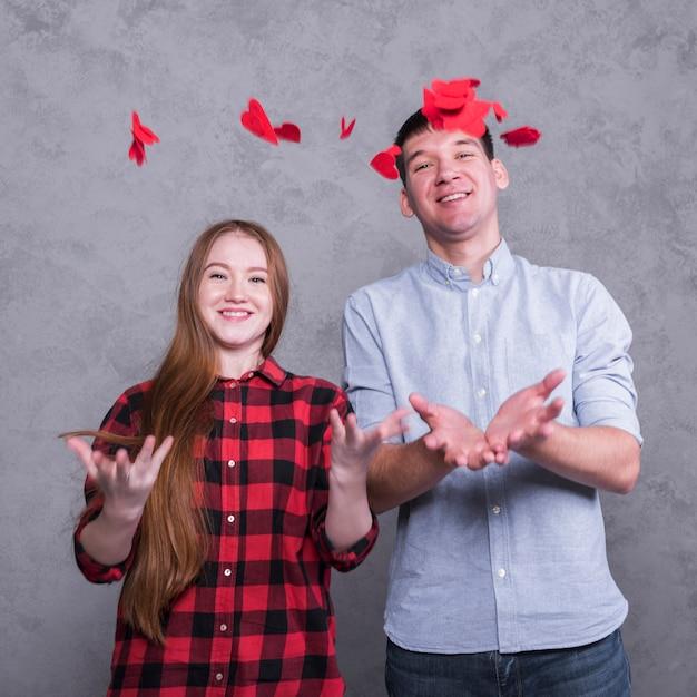 Couple vomir des coeurs de papier rouge Photo gratuit