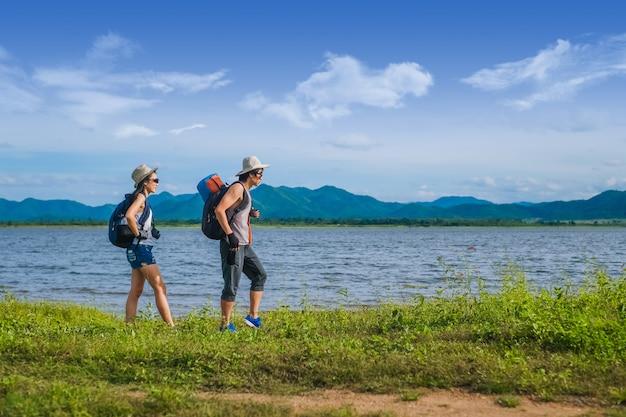 Couple voyageur marchant près du lac dans la montagne Photo Premium