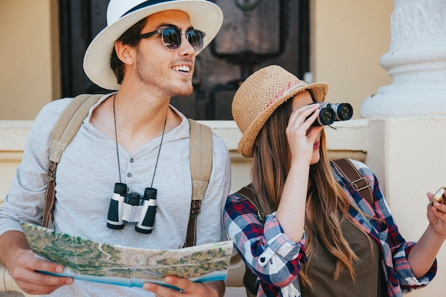 Couple de voyageurs avec des jumelles, des cartes et des lunettes de soleil Photo gratuit