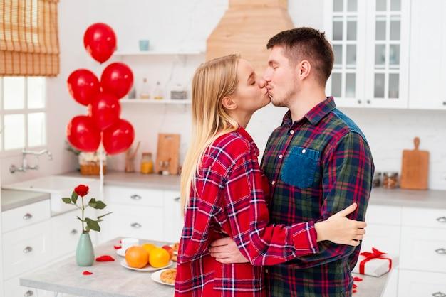 Couple vue de côté s'embrasser dans la cuisine Photo gratuit