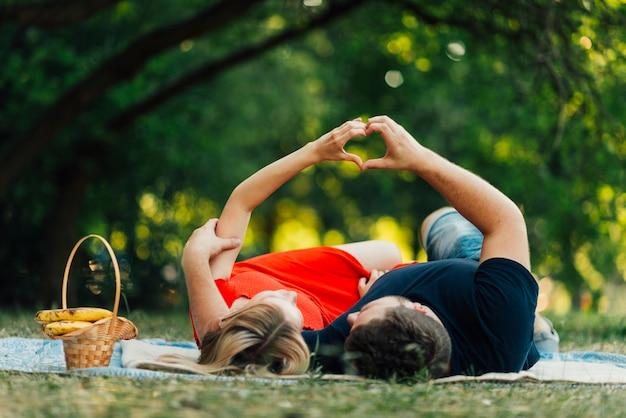 Couple vue de face en forme de cœur dans les airs Photo gratuit
