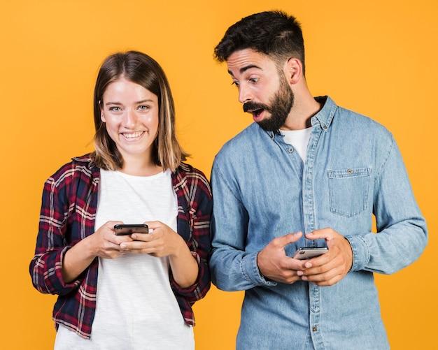 Couple vue de face avec leurs téléphones Photo gratuit