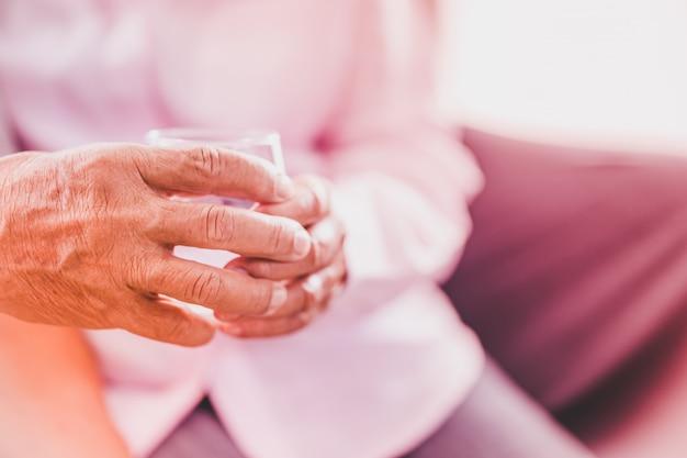 Couples asiatiques âgés prennent la pilule avec un verre d'eau, mise au point sélective Photo Premium