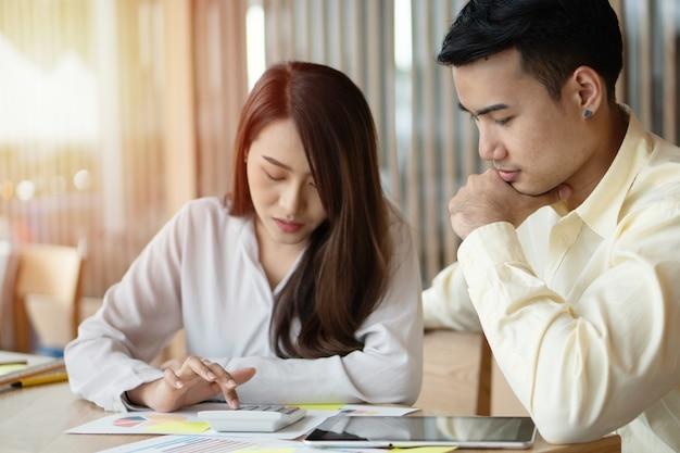 Des couples asiatiques malheureux calculent leurs revenus et leurs dépenses afin de réduire les dépenses inutiles. Photo Premium