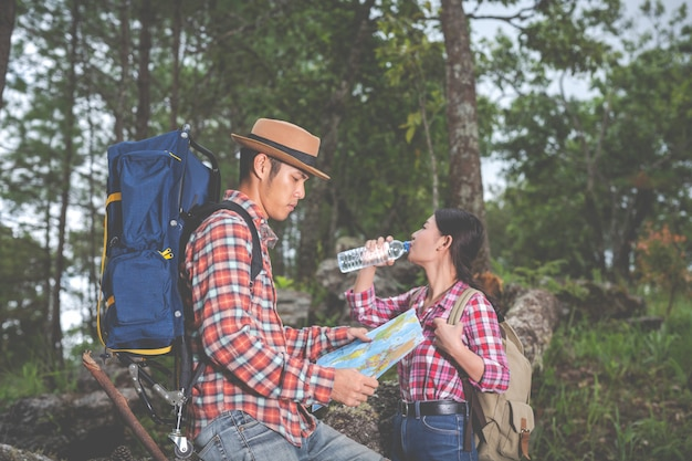 Les couples boivent de l'eau et voient une carte dans la forêt tropicale avec des sacs à dos dans la forêt. aventure, voyages, escalade, randonnée. Photo gratuit