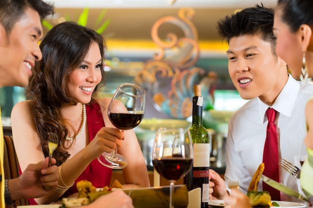 Couples chinois portant un verre de vin au restaurant Photo Premium