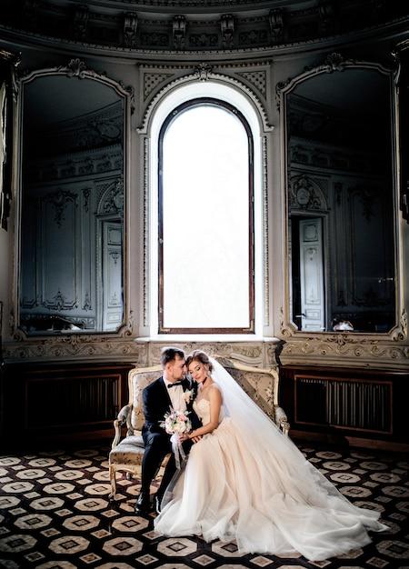 Couples de mariage câlins sur le canapé assis devant une grande fenêtre lumineuse dans un vieux hall de luxe Photo gratuit