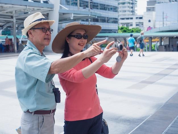 Couples personnes âgées voyageant en ville, un homme et une femme aînés prennent une photo en caméra Photo Premium