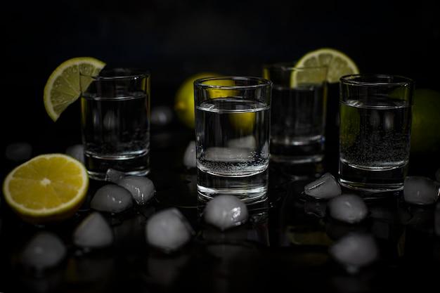 Coups d'alcool avec citron vert et glaçons sur fond noir Photo gratuit