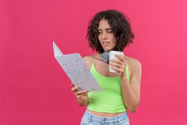 Une Courageuse Jeune Jolie Femme Aux Cheveux Courts En Vert Crop Top Dans Les écouteurs Tenant Une Tasse En Plastique De Café En Regardant Une Carte Avec Confiance Photo gratuit