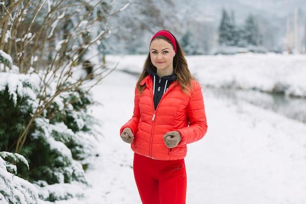 Coureur féminin jogging dans la neige Photo gratuit