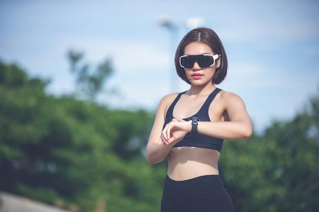 Coureur Féminin Vérifiant Le Suivi De La Condition Physique De La Montre Intelligente Et Souriant Après Les Jambes De Jogging Et De Coureurs Photo Premium