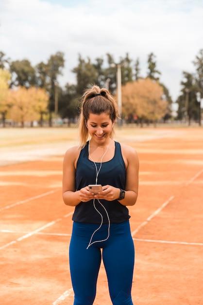 Coureur femme écoutant de la musique Photo gratuit