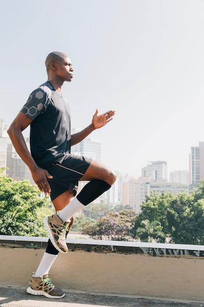 Coureur de femme jeune fitness se réchauffer avant de courir sur le toit Photo gratuit