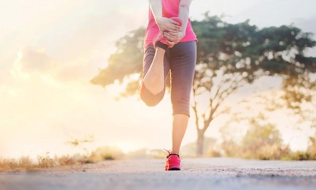 Coureur de la jeune femme qui s'étend de jambes avant de courir au sentier rural du coucher du soleil. Photo Premium
