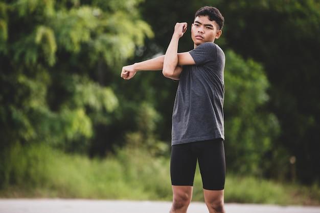 Coureur masculin faisant des exercices d'étirement, se préparant à l'entraînement Photo gratuit