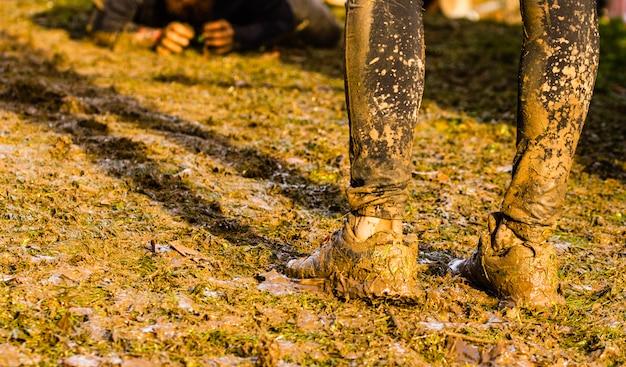 Coureurs de course de boue passant sous des obstacles de barbelés lors d'une course d'obstacles extrême Photo Premium