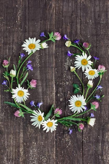 Couronne de camomille et de fleurs simples sur le fond d'un vieil arbre Photo Premium